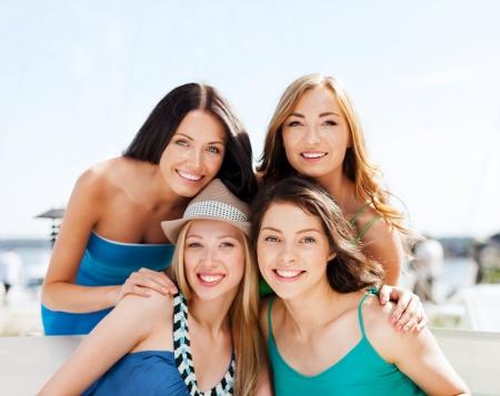 mujeres felices: vacaciones de verano y vacaciones - grupo de chicas en la cafeter�a en la playa