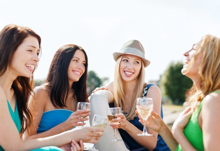 Drinking wine: summer holidays and vacation - girls with champagne glasses on boat or yacht Stock Photo