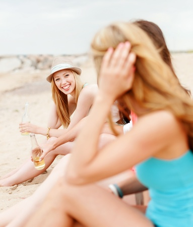 summer holidays and vacation concept - girl with drink and friends on the beach photo