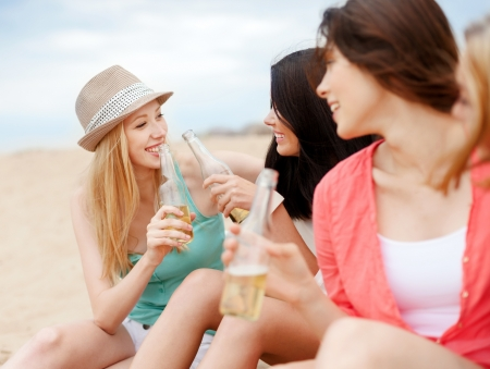 nonalcoholic beer: summer holidays and vacation concept - girls with drinks on the beach
