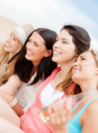 women friends: summer holidays and vacation concept - girls with drinks on the beach