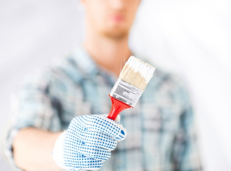 painting and decorating: interior design and home renovation concept - man hand with paintbrush