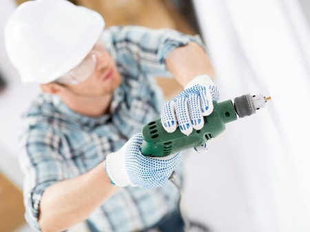 home builder: interior design and home renovation concept - man in helmet with electric drill making hole in wall Stock Photo