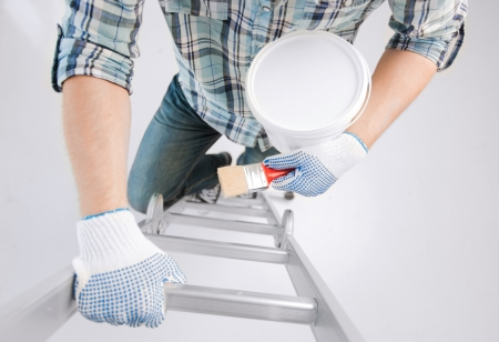 interior design and home renovation concept - man with paintbrush and paint pot climbing ladder photo