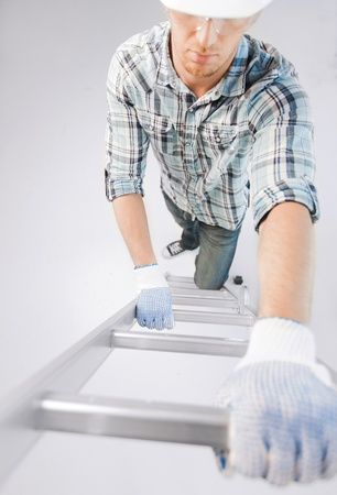 interior design and home renovation concept - man in helmet and gloves climbing ladder photo