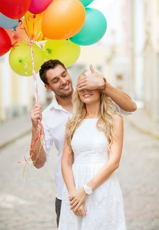 eyes closing: summer holidays, celebration and dating concept - couple with colorful balloons in the city Stock Photo