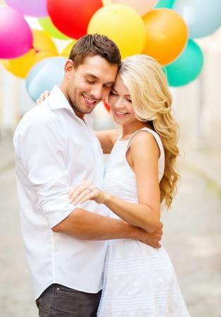 Letní prázdniny, oslavy a svatební koncept - pár s barevnými balónky a zásnubní prsten