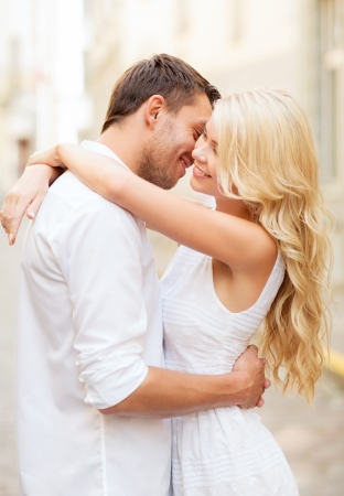 young couple kissing: summer holidays and dating concept - couple in the city