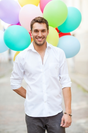 man flying: summer holidays, celebration and lifestyle concept - man with colorful balloons in the city