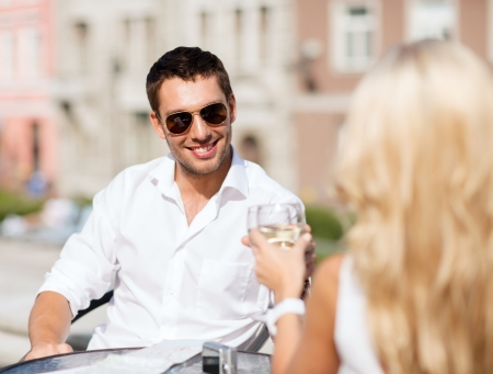 summer holidays and dating concept - man drinking wine with woman in cafe in the city photo
