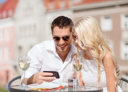 dating: summer holidays, dating and technology concept - couple looking at smartphone in cafe in the city Stock Photo