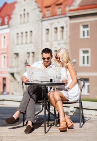 people travelling: summer holidays, dating and tourism concept - couple with map in cafe in the city Stock Photo