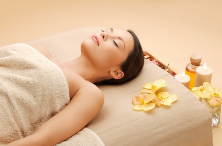 aging: spa and beauty concept - woman in spa salon lying on the massage desk