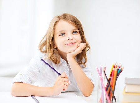 education and school concept - little student girl drawing with pencils at school photo