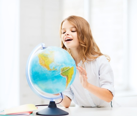 scholar: education and school concept - little student girl with globe at school