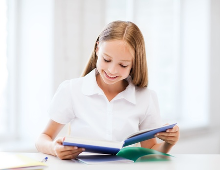 education and school concept - little student girl studying at school Stock Photo - 21680813