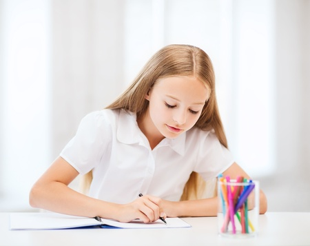 kids writing: education and school concept - little student girl drawing at school