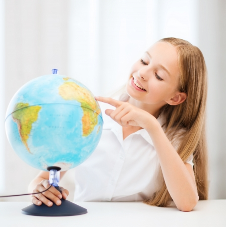 education and school concept - little student girl with globe at school photo