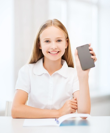 education, school, technology and internet concept - little student girl with smartphone at school photo