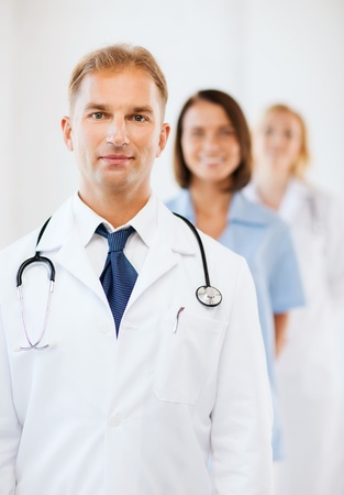 healthcare and medical concept - male doctor with stethoscope and colleagues photo
