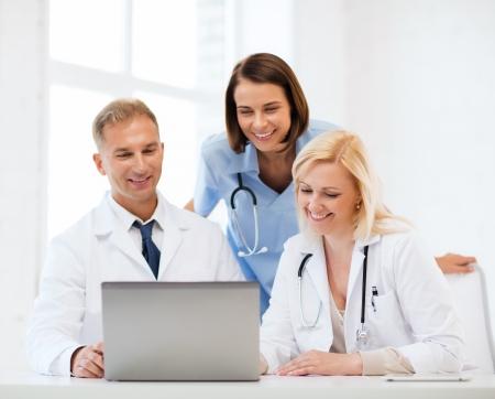 asistencia sanitaria, m�dica y tecnolog�a concepto - grupo de m�dicos mirando port�til Foto de archivo