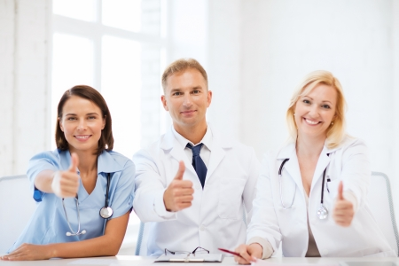 healthcare and medical concept - group of doctors on a meeting showing thumbs up photo