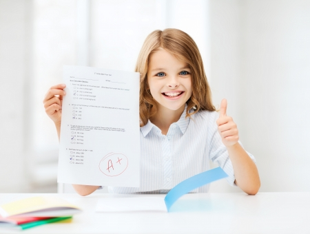 education and school concept - little student girl with test and A grade showing thumbs up at school photo