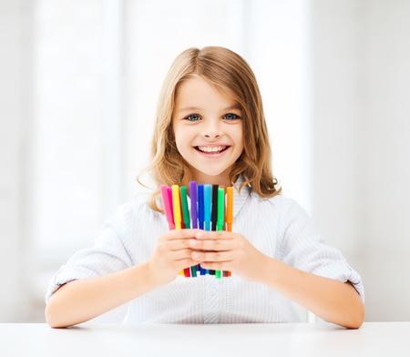 niños estudiando: la educación y la escuela concepto - niña estudiante mostrando coloridos rotuladores en la escuela