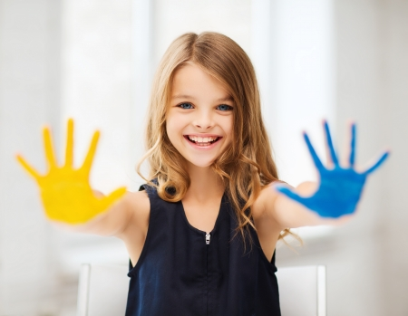 education, school, art and painitng concept - little student girl showing painted hands at school photo