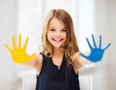 La educación, la escuela, el arte y el concepto painitng - niña estudiante que muestra las manos pintadas en la escuela Foto de archivo - 21680996