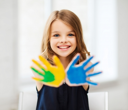happy children: education, school, art and painitng concept - little student girl showing painted hands at school