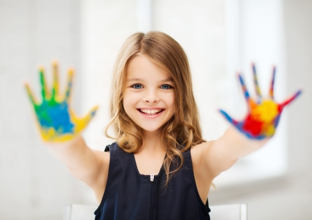 La educación, la escuela, el arte y el concepto painitng - niña estudiante que muestra las manos pintadas en la escuela Foto de archivo - 21681000