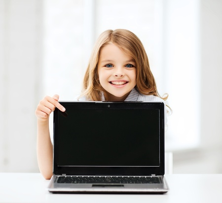 school desk: education, school, technology and internet concept - little student girl pointing at laptop pc at school Stock Photo
