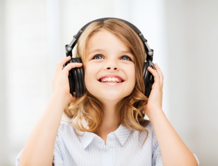 home, technology and music concept - little girl with headphones at home Stok Fotoğraf