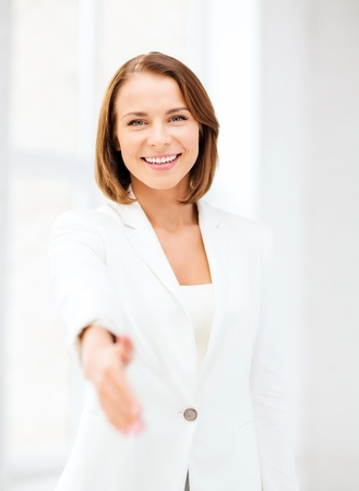 business and partnership concept - businesswoman with an open hand ready for handshake photo