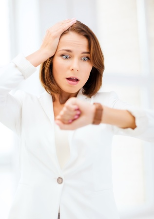 business and time management concept - stressed businesswoman looking at clock photo