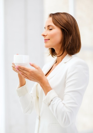 business concept - businesswoman with cup of coffee in office photo