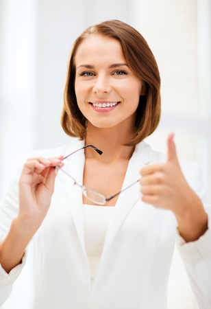 nonsurgical: business and vision correction concept - businesswoman with eyeglasses showing thumbs up in office