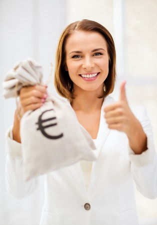 business and money concept - young businesswoman holding money bag with euro photo