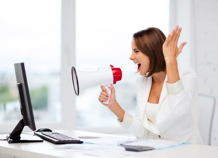 business en technologie concept - strenge zakenvrouw schreeuwen in megafoon in het kantoor Stockfoto