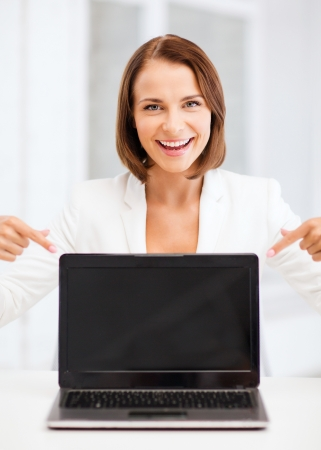 education, business, technology and internet concept - smiling woman with laptop pc photo