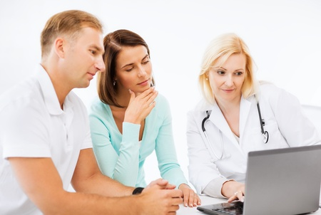 healthcare, medical and technology concept - doctor with patients looking at laptop photo