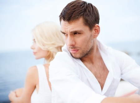 breaking up: summer holidays, dating and relationships concept - stressed man with woman outside