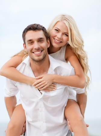 carrying girlfriend: summer holiday, vacation, dating and tourism concept - happy couple having fun on the beach Stock Photo
