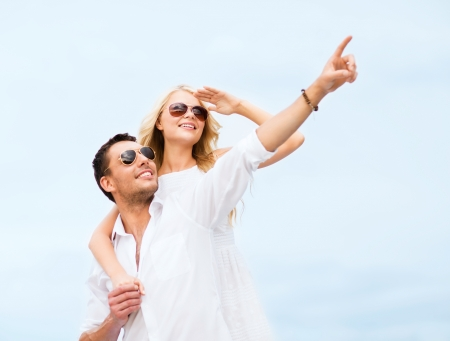 summer holidays and dating concept - couple in shades at sea side photo