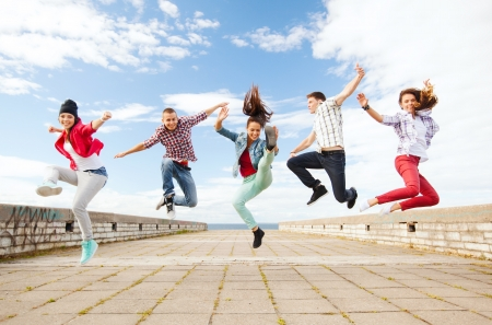 summer, sport, dancing and teenage lifestyle concept - group of teenagers jumping photo