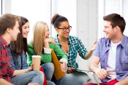 personas comunicandose: concepto de la educación - los estudiantes se comunican y riendo en la escuela