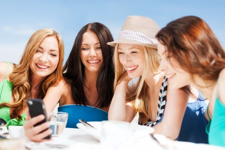 mobile communication: summer holidays, vacation and technology - girls looking at smartphone in cafe on the beach