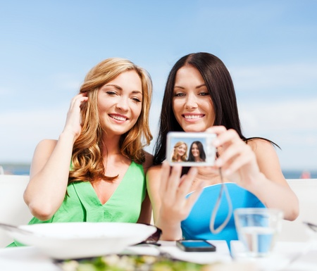 summer holidays, vacation and technology - girls taking photo with digital camera in cafe on the beach photo