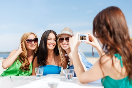summer holidays and vacation - girls taking photo with digital camera in cafe on the beach photo